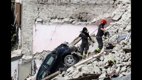 Rescuers make their way through destroyed houses in Pescara del Tronto on Thursday, August 25. It's unclear how many people remain trapped under debris.