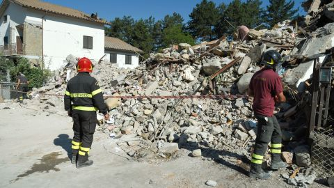 Firefighters cordon off an area around the rubble from a destroyed building in Amatrice on August 26.