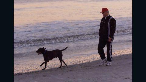 Clinton walks Buddy along the beach during sunset in Hilton Head, South Carolina, on December 30, 1992.
