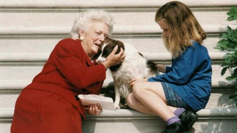 First lady Barbara Bush talks to her dog, Millie, as she and granddaughter Barbara Bush wait for President George H.W. Bush to return to the White House on September 13, 1991.