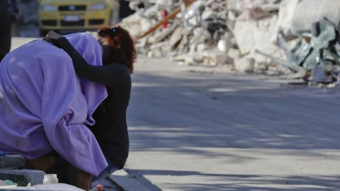 A man and woman comfort each other in front of a collapsed house in Amatrice on August 26.