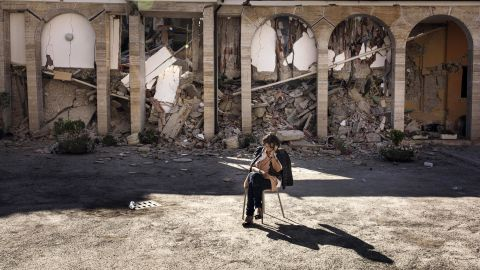 A woman rests in the courtyard of a convent in Amatrice on August 26.