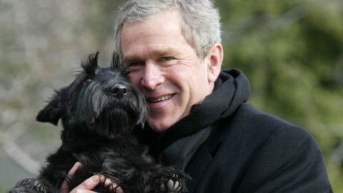 President George W. Bush holds up his dog, Barney, upon arriving at the South Lawn of the White House on February 3, 2002.