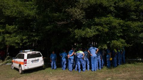 Rescuers congregate in the shade near a temporary camp under construction for residents displaced by the earthquake in Amatrice.