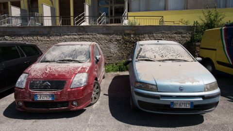 Cars caked in a layer of thick debris dust are parked in central Amatrice.