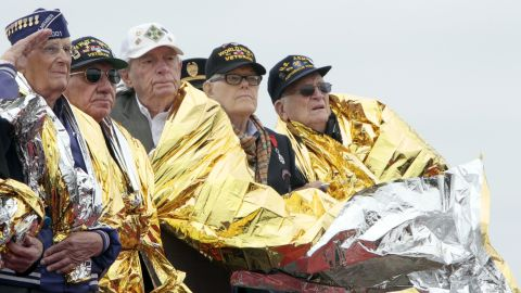 U.S. veterans use space blankets to keep warm at a D-Day commemoration in Normandy, France.