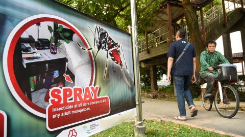 Residents are seen past a public service announcement banner against the spread of Aedes mosquitoes, a carrier for the Zika virus, at a residential block at Aljunied Crescent neighbourhood in Singapore on August 29, 2016.    Singapore on August 28 confirmed 41 locally transmitted cases of the Zika virus, which can cause deformities in unborn babies, and said more infections are likely. / AFP / ROSLAN RAHMAN        (Photo credit should read ROSLAN RAHMAN/AFP/Getty Images)