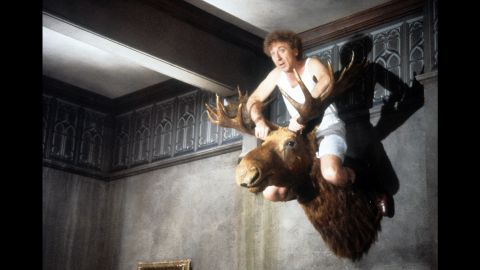 """Wilder sits atop a mounted moose head in a scene from """"Haunted Hollywood,"""" a film he directed in 1986."""