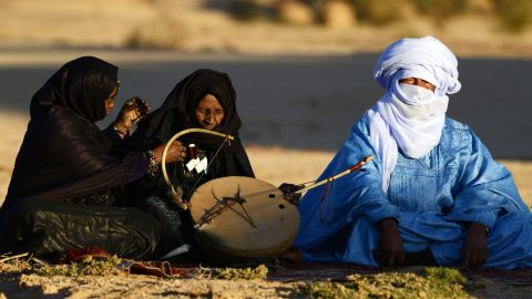 """Tuareg Khoulene Alamine (center), an imzad teacher sits with a poet on the sand of the Tagmart plateau. The imzad, a single-stringed violin played only by Tuareg women, is making a comeback in Algeria. Jubber experienced a wealth of cultures that rubbed off on each other across the Sahara. """"I love not only the richness of the individual cultures,"""" he said, """"but the way they intersect with each other in a matrix of interrelatedness."""""""