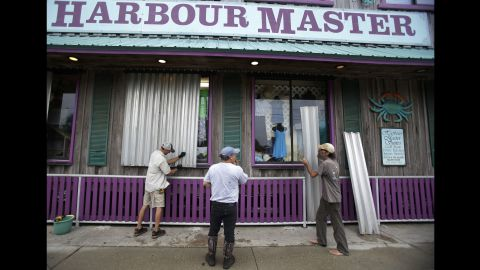 Workers in Cedar Key install storm shutters on a storefront as they prepare for Hermine on September 1.