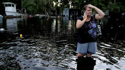 Lynne Garrett speaks to loved ones as she surveys damage outside of her home in St. Marks, Florida, on Friday, September 2.
