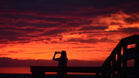 Karen Duer-Potts uses her cellphone to take a photograph of the sunset as the outer band of Hermine creeps over the beach at Cape Charles, Virginia, on September 2.