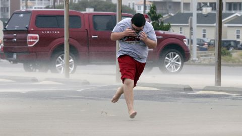 Eli White covers his face from the blowing sand in Nags Head, North Carolina, Saturday, September 3, as the tail of Tropical Storm Hermine passes the Outer Banks. Hermine hit Florida's Gulf Coast on Friday as a hurricane but has since weakened.