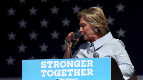 Democratic presidential nominee former Secretary of State Hillary Clinton pauses to take a drink of water to help soothe a cough during a campaign rally at Luke Easter Park on September 5, 2016 in Cleveland, Ohio.
