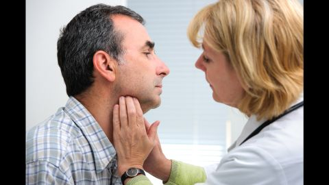 female doctor touching the throat of a patient in the office; Shutterstock ID 206475955