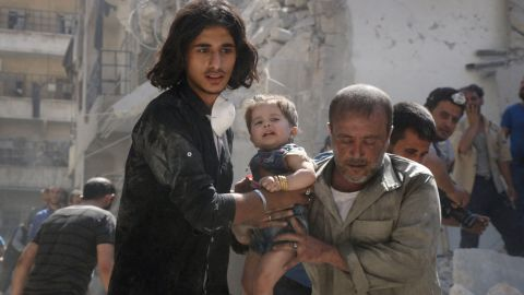 A Syrian civil defence member and a volunteer carry a little girl rescued from under the rubble of destroyed buildings following a reported airstrike on the rebel-held Salihin neighbourhood of the northern city of Aleppo, on September 10, 2016.  The Syrian opposition on September 10 cautiously welcomed a ceasefire deal agreed by Moscow and Washington that could also see the first joint military campaign by the two powers against jihadists. / AFP / THAER MOHAMMED        (Photo credit should read THAER MOHAMMED/AFP/Getty Images)