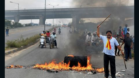 An activist stands beside a traffic blockade at a major connecting road during a statewide strike in Bangalore.