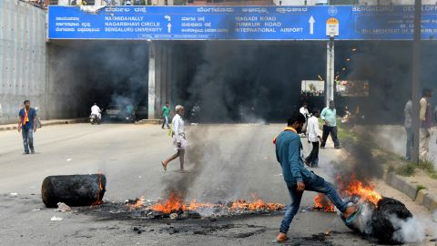 An Indian activist removes a traffic blockade on a major connecting road during a statewide strike in Bangalore on September 9, 2016.