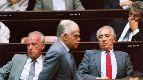 Right-wing Israeli Premier Yitzhak Shamir, center, walks past Labor party leaders Yitzhak Rabin, left, and Shimon Peres during a special Knesset summer session meeting on May 7, 1990, in Jerusalem.
