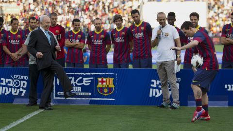 Israeli President Shimon Peres kicks the ball to FC Barcelona's striker Lionel Messi during a soccer clinic in Broomfield Stadium in Tel Aviv on August 4, 2013.
