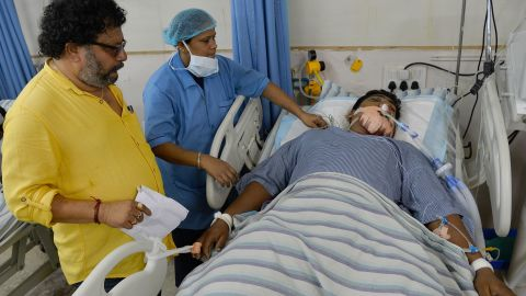 A family friend and a nurse attend to Kumar, a 32-year-old patient in a private hospital in Bangalore. Kumar was injured in the violence that erupted following the Cauvery water dispute.
