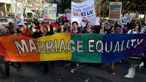 Pro-gay marriage supporters carry a rainbow banner and flags during a rally in Sydney on June 25, 2016. Hundreds of supporters of gay marriage marched through the streets of the central business district of Sydney for their rights. / AFP / SAEED KHAN        (Photo credit should read SAEED KHAN/AFP/Getty Images)