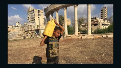 A child carries a canister filled with water near Aleppo's Castello Road.