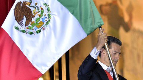 President Enrique Pena Nieto waves the Mexican National Flag.