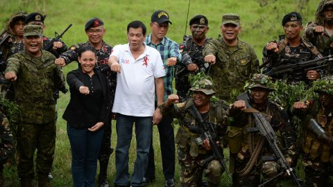 Philippine President Rodrigo Duterte (4th L, in white) raises a clenched fist with Secretary of Defense Delfin Lorenzana (5th L, in checkered shirt) and military chief General Ricardo Visaya (3rd R, back row) as he poses for photos with members of the Scout Rangers regiment at a military training camp in San Miguel town, Bulacan province, north of Manila on September 15, 2016.    Rodrigo Duterte shot dead a justice department employee and ordered the murder of opponents, a former death squad member told parliament September 15, in explosive allegations against the Philippine president. / AFP / TED ALJIBE        (Photo credit should read TED ALJIBE/AFP/Getty Images)