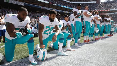 From left, Miami Dolphins' Jelani Jenkins, Arian Foster, Michael Thomas and Kenny Stills kneel during the singing of the national anthem before a game against the Seattle Seahawks on September 11, 2016.