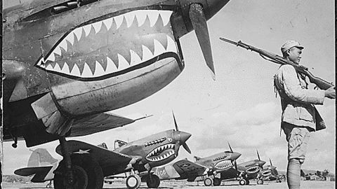 A Chinese soldier guards P-40 AVG Flying Tigers at an airfield somewhere in China.