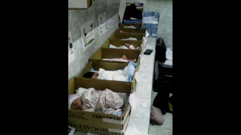 A row of cardboard boxes on a counter -- inside each box, a newborn baby.
