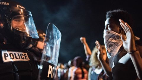 Police officers face off with protestors on Interstate 85 during protests following the death of a man shot by a police officer on Wednesday, September 21, in Charlotte, North Carolina. Violent protests erupted overnight following the fatal shooting of 43-year-old Keith Lamont Scott while trying to serve a warrant for a different man at an apartment complex.