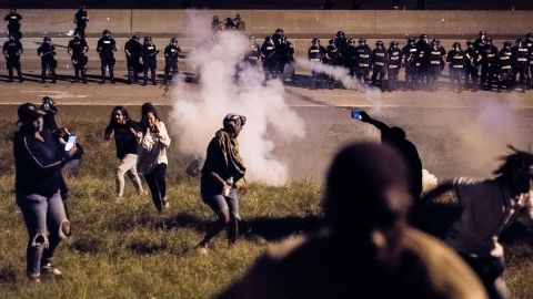 Protesters run from a gas canister after blocking traffic on I-85.