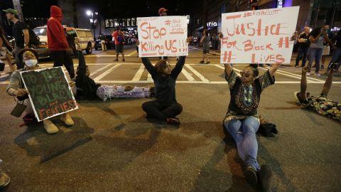 Demonstrators hold Black Lives Matter signs.