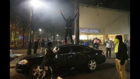 A protester stands on a car roof.