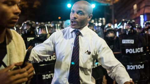"""Charlotte public defender Toussaint Romain pushes a protester back from a line of police. """"We can't lose any more lives, man. I'm a public defender. I can't represent any more people,"""" <a href=""""http://www.cnn.com/2016/09/21/us/public-defender-toussaint-romain-charlotte-protests/index.html"""" target=""""_blank"""">he told CNN's Boris Sanchez.</a>"""