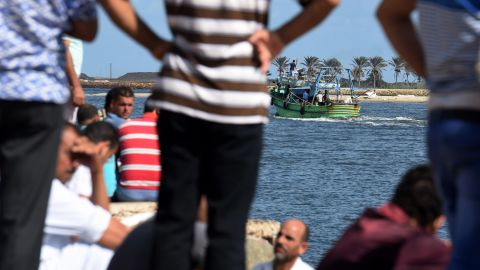 Egyptian men sit along the shore in the Egyptian port city of Rosetta on September 22, 2016 as they watch a boat departing for a search operation.