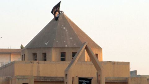 """The flag of the Islamic State of Iraq and the Levant (ISIL) flutters on the """"dome"""" of the  Armenian Catholic Church of the Martyrs in the northern rebel-held Syrian city of Raqqa on September 28, 2013."""