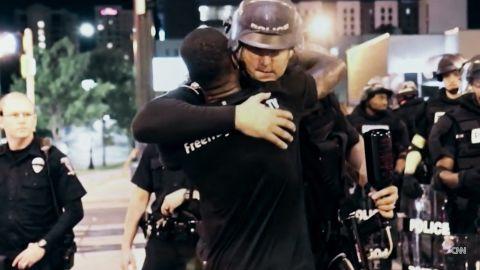 Ken Nwadike hugs an officer in Charlotte on Wednesday night.