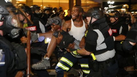 """Police officers and protesters carry a man who was shot during the second night of protests on Wednesday, September 21. The shooting victim, 26-year-old Justin Carr, later died. Police <a href=""""http://www.cnn.com/2016/09/23/us/charlotte-protests/index.html"""" target=""""_blank"""">have charged another civilian</a> in connection with Carr's death."""