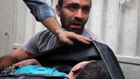 A Syrian man carries the body of his nephew, recovered from the rubble.
