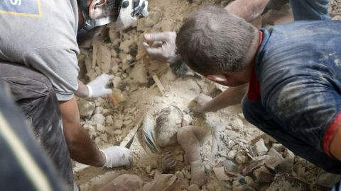 The Syrian Civil Defense, also known as the White Helmets, work to save 8-month-old Muhammad Sawas from under the rubble. But it was too late.