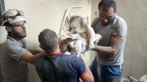 The volunteers remove an infant's body from the destroyed building.