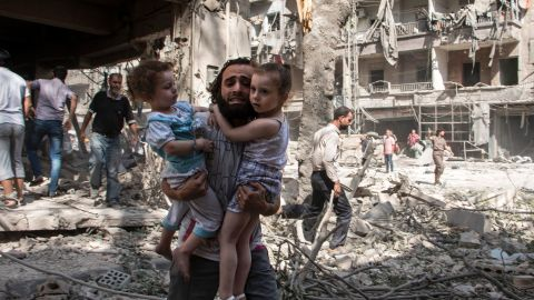 A Syrian man carries his two girls as he walks across the rubble following a barrel bomb attack on the rebel-held neighbourhood of al-Kalasa in the northern Syrian city of Aleppo on September 17, 2015. Once Syria's economic powerhouse, Aleppo has been ravaged by fighting since the rebels seized the east of the city in 2012, confining government forces to the west. AFP PHOTO / KARAM AL-MASRI / AFP / KARAM AL-MASRI AND -        (Photo credit should read KARAM AL-MASRI/AFP/Getty Images)