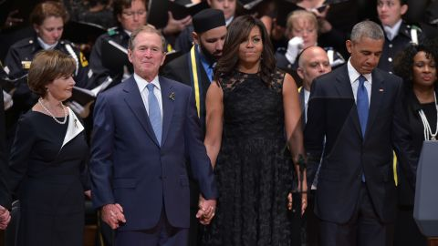"""The Bushes and the Obamas join hands during the singing of """"The Battle Hymn of the Republic"""" during an interfaith memorial service for the victims of the Dallas police shooting on July 12, 2016, in Dallas."""