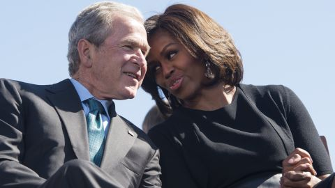 Former President George W. Bush speaks with first lady Michelle Obama during an event marking the 50th anniversary of the Selma to Montgomery civil rights marches at the Edmund Pettus Bridge in Selma, Alabama, on March 7, 2015.