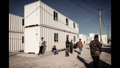"""Migrants walk past housing containers in """"The Jungle"""" on Tuesday, February 16."""
