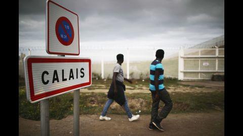 Migrants walk past security fencing on Tuesday, September 6.