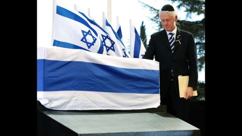 """Clinton touches Peres' coffin. Clinton spoke fondly of Peres, adding in his eulogy: """"He knew exactly what he was doing in being overly optimistic. ... He never gave up on anybody, I mean anybody."""""""